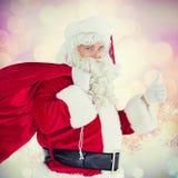Immagine composita di Santa positiva con il suoi sacco e pollici su Fotografie Stock Libere da Diritti