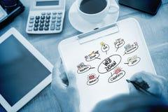 Immagine composita di scrittura dell'uomo sulla lavagna per appunti sullo scrittorio funzionante Fotografie Stock Libere da Diritti