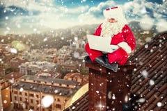 Immagine composita di seduta e di per mezzo di Santa del suo computer portatile Fotografie Stock
