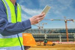 Immagine con la tenuta ed il touch screen maschii della mano con l'invio del testo sullo Smart Phone, compressa, cellulare sopra  Fotografie Stock