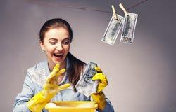 Immagine concettuale su cui i soldi ombreggiati del lavare della donna immagini stock libere da diritti