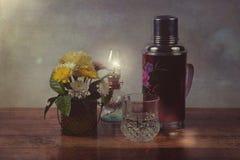 Immagine d'annata dei fiori e della bottiglia antica Immagini Stock
