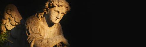 Immagine d'annata di un angelo triste su un cimitero nell'ombra Fotografie Stock