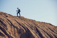 Immagine da lontano dalla parte posteriore dell'uomo con lo zaino ed i bastoni da passeggio Fotografia Stock Libera da Diritti