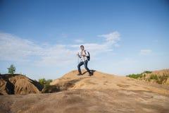 Immagine da lontano dell'uomo turistico con i bastoni da passeggio sulla collina della montagna Fotografie Stock