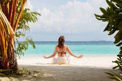 Immagine dalla parte posteriore di una giovane donna che medita su spiaggia in Maldive fotografia stock