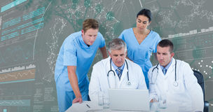 immagine 3DComposite del gruppo di medici che per mezzo del computer portatile allo scrittorio Fotografia Stock Libera da Diritti