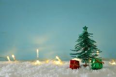 Immagine degli alberi di Natale di carta sopra neve bianca e le luci dorate della ghirlanda fotografia stock