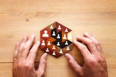 immagine dei blocchetti di puzzle del tangram con le icone della gente sopra la tavola di legno, le risorse umane ed il concetto  Fotografia Stock