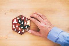 immagine dei blocchetti di puzzle del tangram con le icone della gente sopra la tavola di legno, le risorse umane ed il concetto  Fotografia Stock Libera da Diritti