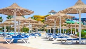 Immagine dei lettini e dei parasoli della canna vicino al poolzone ad un'area dell'hotel fotografia stock