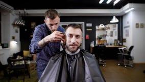 Immagine dei pantaloni a vita bassa barbuti che si siede nel parrucchiere coperto di peignoir nero Barbiere vestito in abbigliame stock footage