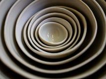 Immagine dei piatti e delle ciotole impilati nel morbido fuoco con un bello tiro del modello con un obiettivo macro fotografie stock