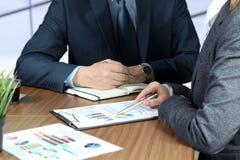 Immagine dei soci commerciali che discutono i documenti e le idee alla riunione Fotografia Stock
