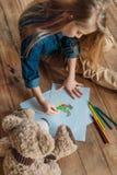 Immagine del disegno della ragazza sul pavimento a casa, bambini che disegnano concetto immagine stock libera da diritti