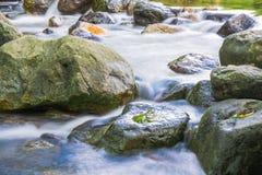 Immagine del fondo degli scorrimenti dell'acqua tramite il percorso roccioso di una corrente Fotografie Stock