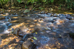 Immagine del fondo degli scorrimenti dell'acqua tramite il percorso roccioso o Fotografia Stock