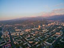 Immagine del fuco sopra la città al tramonto con le montagne Fotografie Stock Libere da Diritti