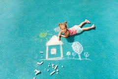 Immagine del gesso di disegno della bambina sulla terra Fotografia Stock Libera da Diritti