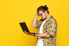 Immagine del giovane confuso con i vetri che tengono testa con la sua mano e che esaminano computer portatile sopra fondo giallo immagine stock libera da diritti