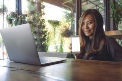 Immagine del modello di bella donna asiatica di affari che tiene e che mostra telefono cellulare bianco con lo schermo in bianco  Fotografia Stock Libera da Diritti