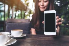 Immagine del modello di bella donna che tiene e che mostra telefono cellulare bianco con lo schermo nero in bianco con le tazze d Immagine Stock Libera da Diritti
