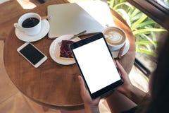 Immagine del modello di vista superiore delle mani che tengono il pc nero della compressa con lo schermo bianco in bianco Fotografia Stock Libera da Diritti