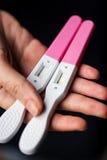 Immagine del primo piano dei test di gravidanza della donna della mano di una casa della tenuta Fotografia Stock Libera da Diritti