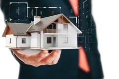 Immagine del primo piano dell'uomo d'affari che tiene una casa 3d Immagini Stock Libere da Diritti