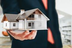 Immagine del primo piano dell'uomo d'affari che tiene una casa 3d Fotografie Stock