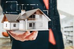Immagine del primo piano dell'uomo d'affari che tiene una casa 3d Immagini Stock
