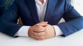 Immagine del primo piano dell'uomo d'affari in vestito blu con le mani piegate che si siedono dietro la scrivania di legno bianca fotografia stock libera da diritti
