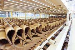 Immagine del primo piano della fila del cartone della piega al fondo della fabbrica Immagine Stock