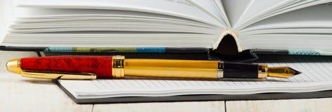 Immagine del primo piano della penna, del taccuino e del libro Immagine Stock
