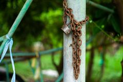 Immagine del primo piano della serratura e della catena arrugginite sulla colonna d'acciaio con il fondo vago del bokeh immagine stock libera da diritti