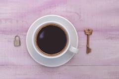 Immagine del primo piano della tazza di caffè con la serratura e la chiave Immagine Stock