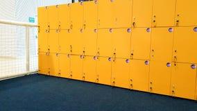 Immagine del primo piano delle file lunghe diritte degli armadi gialli nella scuola o nell'istituto universitario fotografia stock