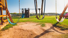 Immagine del primo piano delle oscillazioni vuote sul campo da giuoco dei bambini al giorno soleggiato luminoso Nessuno che gioca fotografie stock