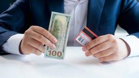 Immagine del primo piano di dubbio dell'uomo d'affari del usando la carta di credito o le banconote tradizionali del biglietto immagine stock