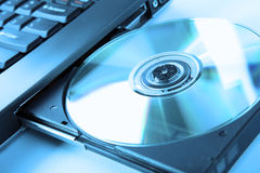 Immagine del primo piano di un computer portatile e di un disco del CD/DVD Fotografia Stock Libera da Diritti