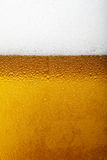 Immagine del primo piano di una birra con schiuma e le bolle Fotografie Stock