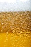 Immagine del primo piano di una birra con schiuma e le bolle Immagini Stock Libere da Diritti