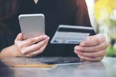 Immagine del primo piano di una carta di credito della tenuta della mano del ` s della donna e di un telefono cellulare usando immagini stock