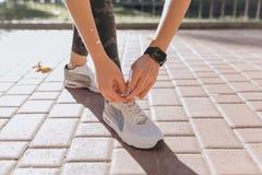 Immagine del primo piano di una femmina dell'atleta che lega i suoi pizzi su un banco al parco Ha piegato giù e vettura di sport  fotografia stock libera da diritti