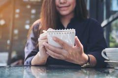 Immagine del primo piano di una tenuta e di una scrittura asiatiche della donna di affari sul taccuino con la tazza di caffè sull Fotografie Stock Libere da Diritti