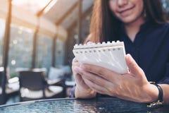 Immagine del primo piano di una tenuta e di una scrittura asiatiche della donna di affari sul taccuino con la tazza di caffè sull Immagine Stock Libera da Diritti