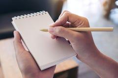 Immagine del primo piano di una tenuta e di una scrittura della mano su un taccuino bianco in bianco Fotografia Stock