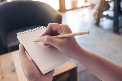 Immagine del primo piano di una tenuta e di una scrittura della mano su un taccuino bianco in bianco Fotografia Stock Libera da Diritti
