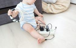 Immagine del primo piano del neonato unatteded che gioca con i cavi elettrici nell'ambito dell'alta tensione a casa Fotografia Stock Libera da Diritti