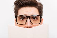 Immagine del primo piano del nerd confuso in occhiali che si nascondono dietro il libro fotografie stock